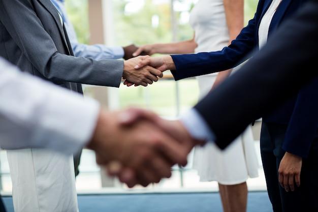 Средняя часть руководителей предприятий пожимают друг другу руки