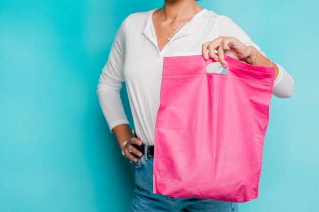 白いポロシャツとフクシアピンクの買い物袋を単独で保持しているブルージーンズのカジュアルな若い女性の中央部