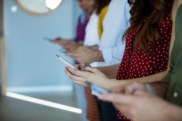 オフィスで携帯電話を使用するクリエイティブビジネスチームの中間セクション