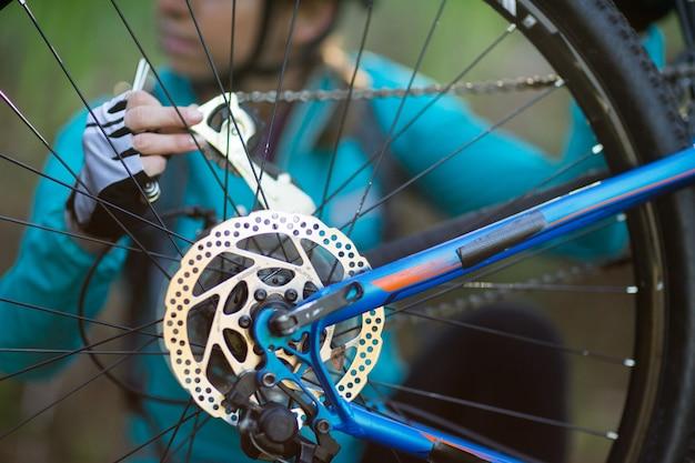Средняя часть женщины-байкера ремонтирует горный велосипед