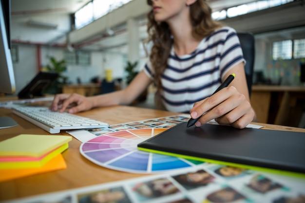 데스크에서 그래픽 태블릿을 사용하는 여성 그래픽 디자이너의 중간 부분