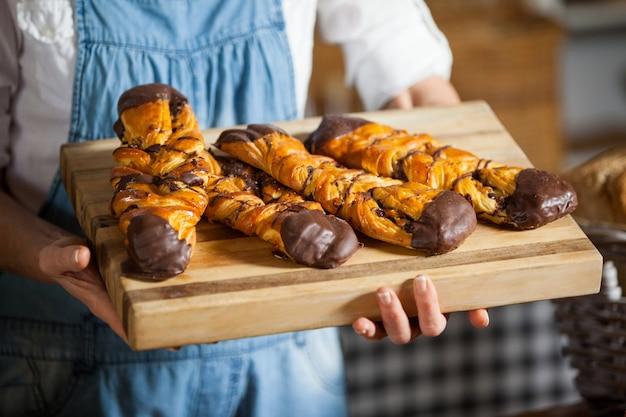 Средняя часть сотрудников женского пола держит сладкие блюда в пекарне