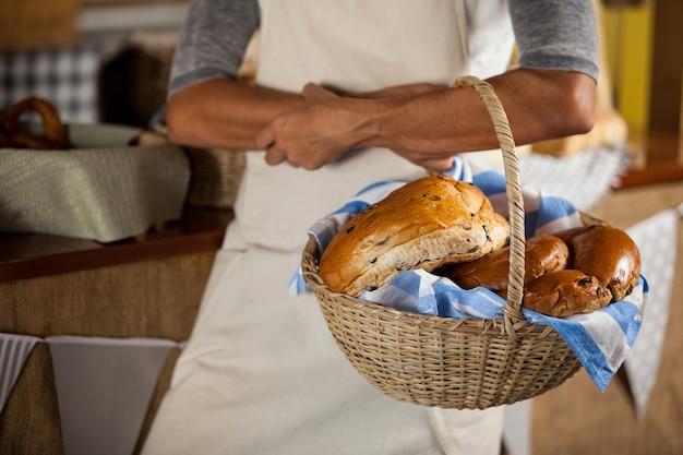 カウンターでパンの枝編み細工品バスケットを保持している女性スタッフの中央部