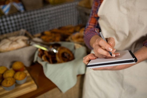 Средняя часть женского персонала, пишущего в блокноте за прилавком хлеба