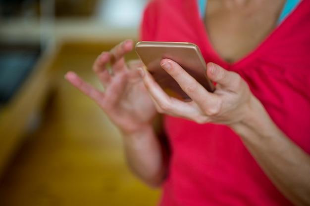 Средняя часть женщины-тренера с помощью мобильного телефона