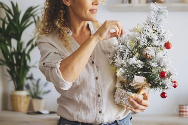 自宅で12月の休日の休暇中に白いクリスマスツリーと幸せな大人の女性の中央セクション。居間を飾るクリスマスと冬の季節を楽しむ屋内女性