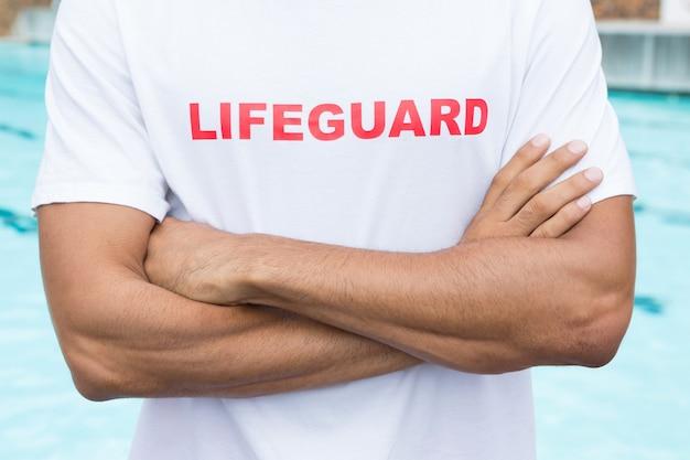 プールサイドで腕を組んで立っているライフガードの中央部