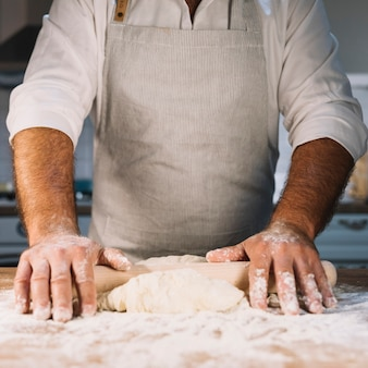 Mid section of male baker flattening the dough