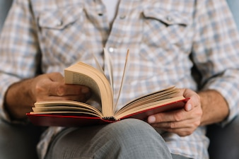 Mid section of man turning the pages of book