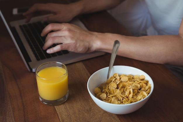 Средняя часть человека, использующего ноутбук во время завтрака в спальне