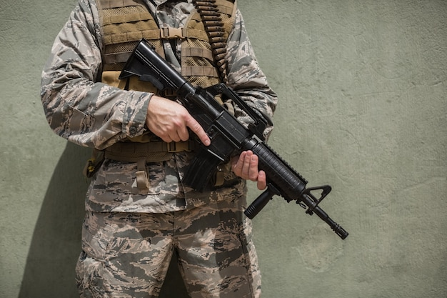 부트 캠프에서 콘크리트 벽에 소총으로 서있는 군인의 중간 부분