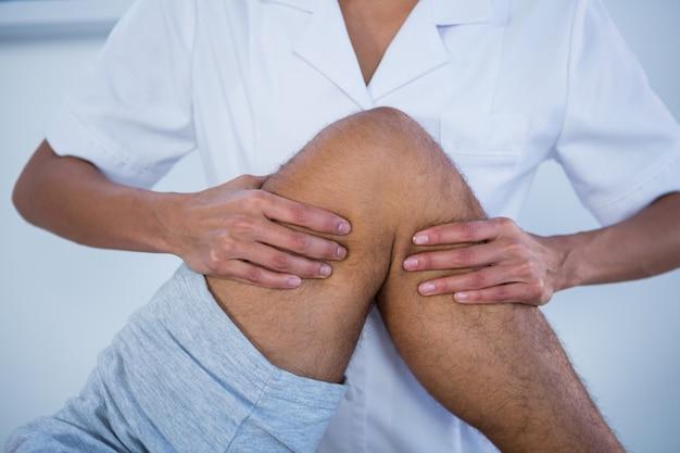 환자에게 다리 마사지를주는 물리 치료사의 중간 부분