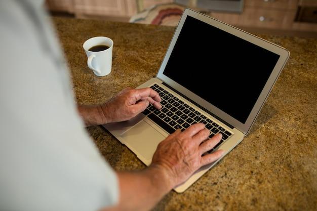 Средняя часть старшего мужчины, использующего ноутбук на кухне дома