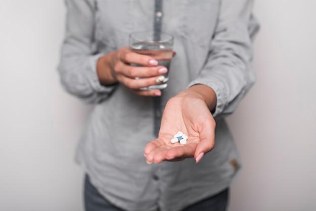 Середина разделе больной женщина, принимая таблетки против серого фона