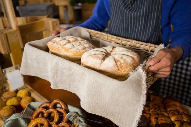 Средняя часть персонала держит плетеную корзину с хлебом у прилавка