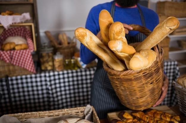 Средняя часть персонала держит плетеную корзину с французским хлебом у прилавка