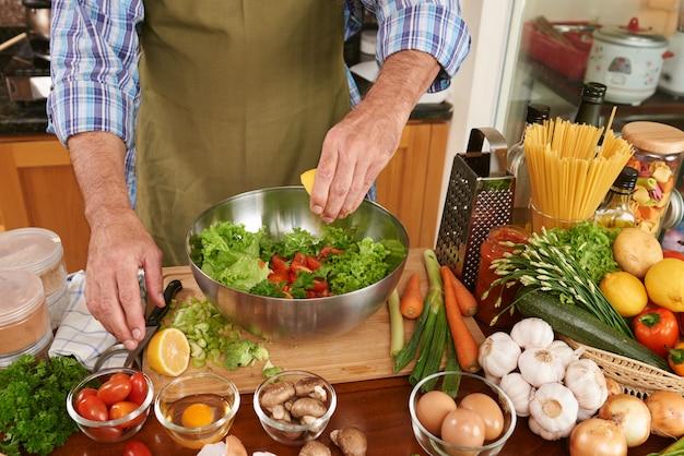 신선한 샐러드에 레몬 주스를 추가하는 앞치마에서 인식 할 수없는 남자의 중간 부분