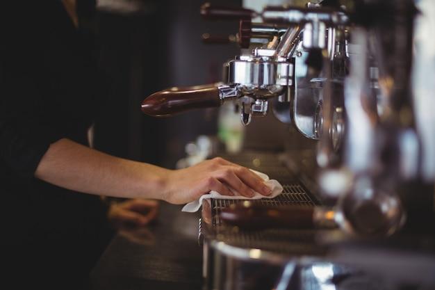Средняя часть официантки вытирает кофеварку с салфеткой в кафе.