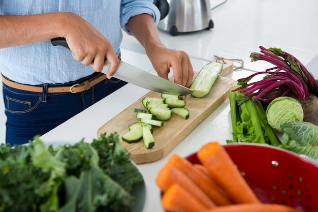 白い背景のまな板で野菜を切る女性の中央部