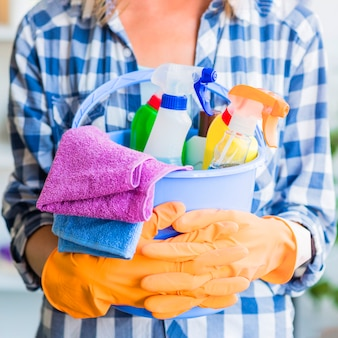 Mid section of woman holding cleaning equipments in the blue bucket