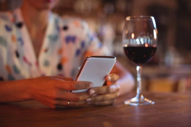 Средняя часть женщины, использующей мобильный телефон