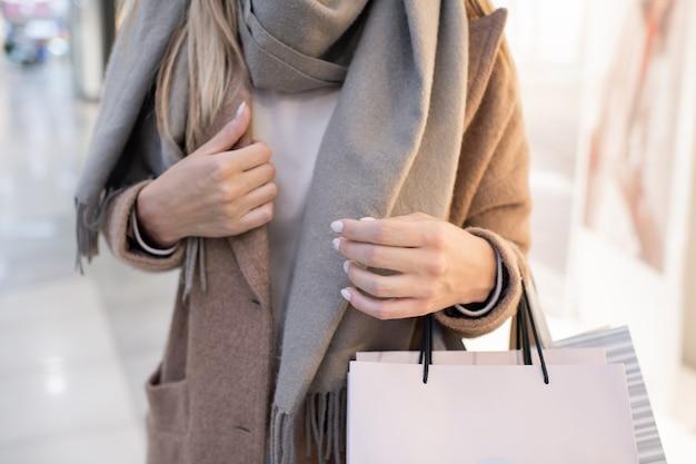 買い物の後、貿易センター内を移動しながら紙袋を運ぶコートとスカーフのスタイリッシュな若い女性の中間セクション