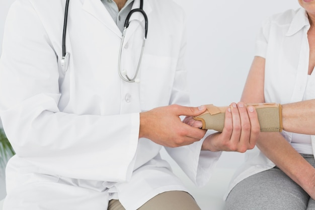 Mid section of a physiotherapist examining a womans wrist