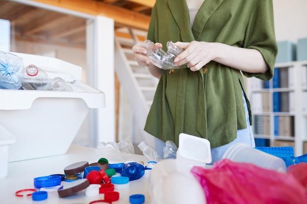 집에서 폐기물을 분류하는 현대 젊은 여성의 중간 섹션 초상화, 전경에서 플라스틱 항목에 초점