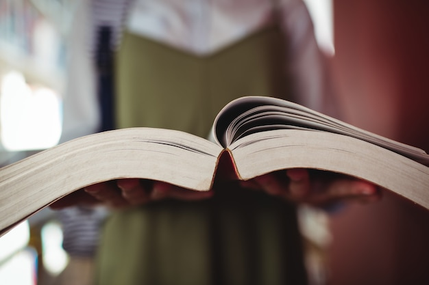 Mid-section of schoolgirl reading book in library