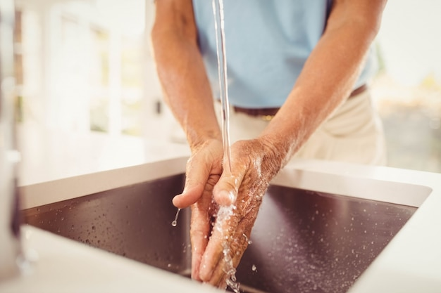 Mid section of senior man washing hands in the kitchen