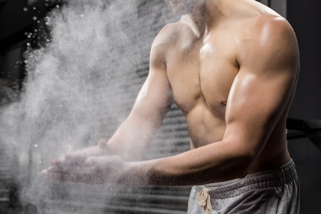 Mid section of shirtless man clapping hands with talc at the  gym