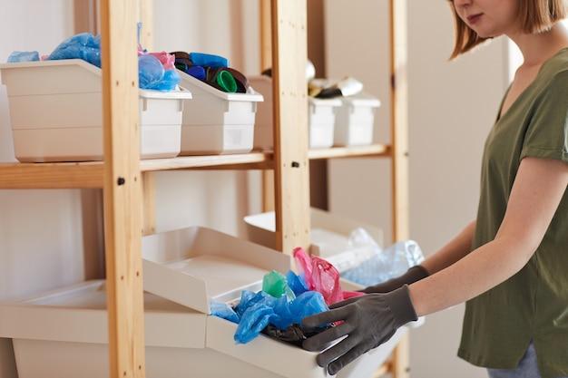 自宅で廃棄物を分別する若い女性の中央断面図、保管とリサイクルの概念