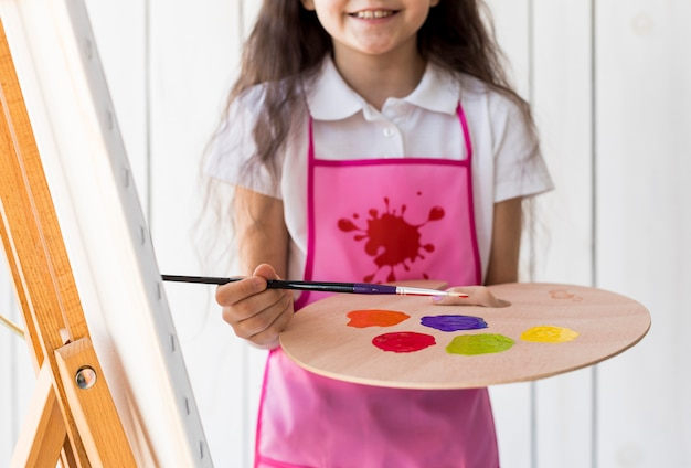 Mid section of a smiling girl holding paintbrush and palette
