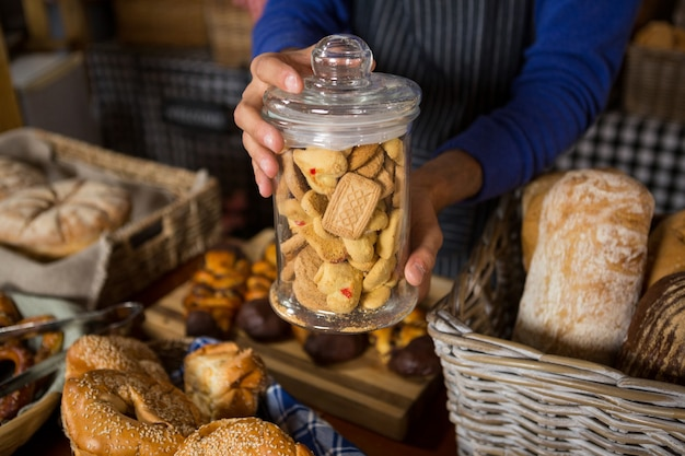 Mid section of staff holding glass jar of cookies at counter