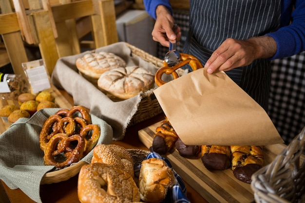 Mid section of staff packing croissant in paper bag at counter