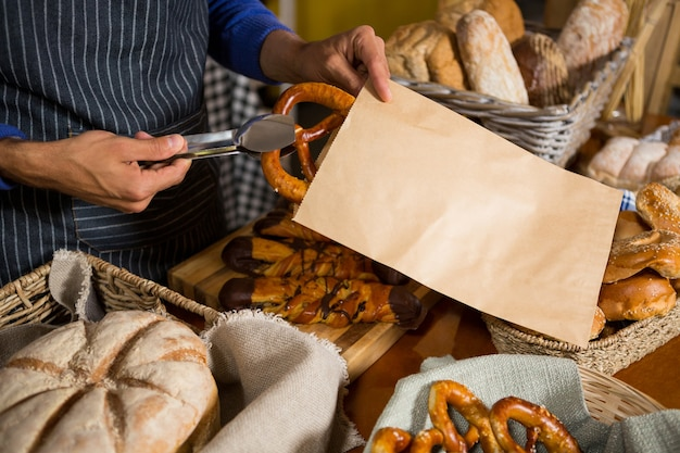 Mid section of staff packing pretzel bread in paper bag at counter