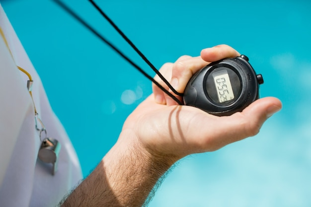 Mid section of swim coach holding stopwatch near poolside