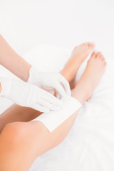 Mid section of therapist waxing womans leg at spa center