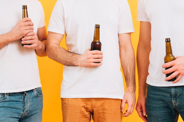 Mid section of three men in white t-shirt holding beer bottle