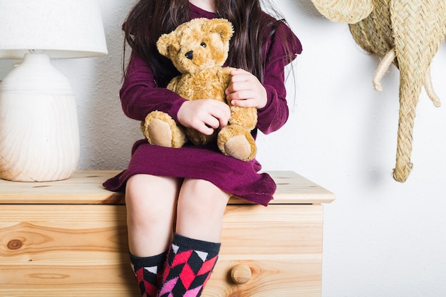 Mid section view of a girl sitting on tabletop with stuffed toy