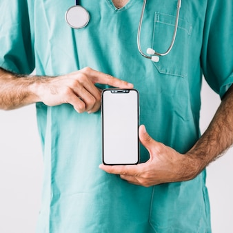 Mid section view of a male doctor holding mobile phone