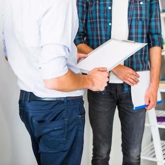 Вид среднего сечения двух бизнесменов с папкой и буфером обмена