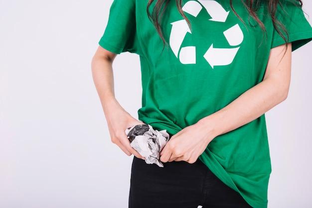 Vista di metà sezione della mano di una donna che mette carta stropicciata in tasca