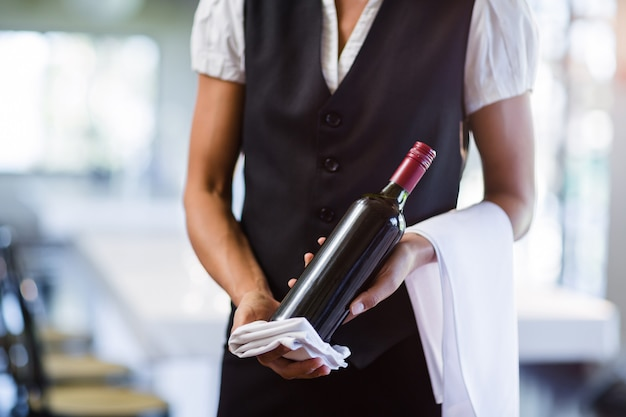 Mid section of waitress holding a bottle of red wine and a towel