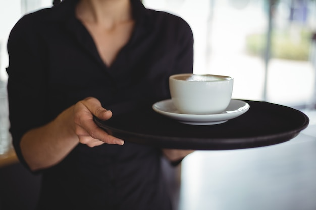 Mid section of waitress standing with cup of coffee