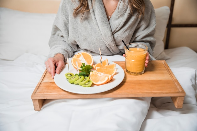 Mid section of a woman having fresh oranges and kiwi slices with glass of juice on bed