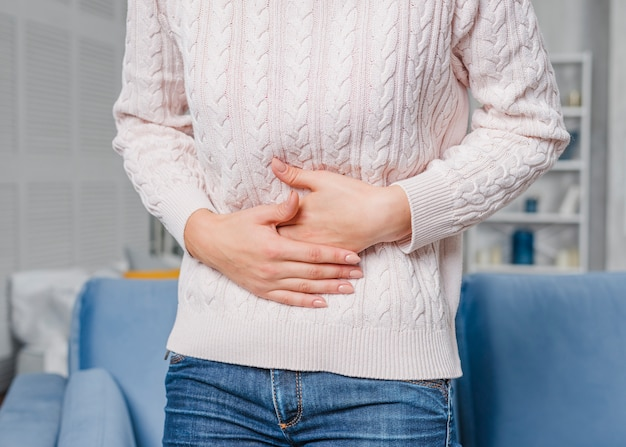 Mid section of woman having stomach ache