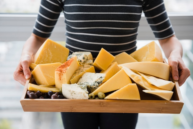 Mid section of woman holding cheese slices in wooden tray