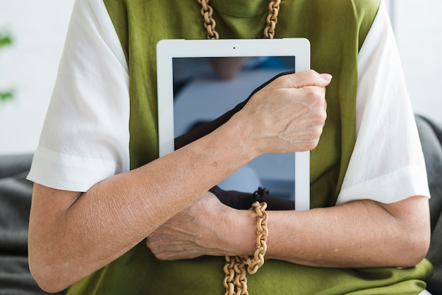 Mid section of woman holding digital tablet