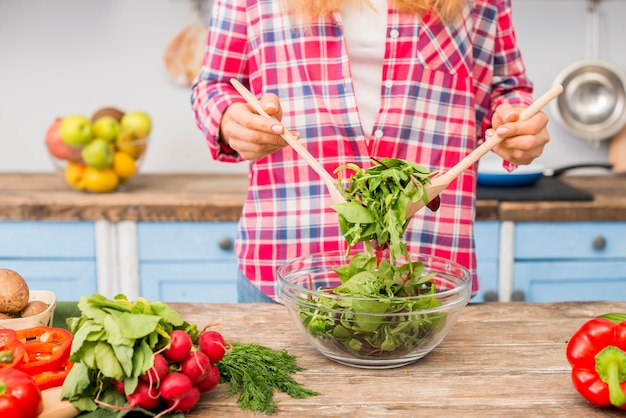 Mid section of a woman holding leafy vegetable salad with wooden spoon on wooden table